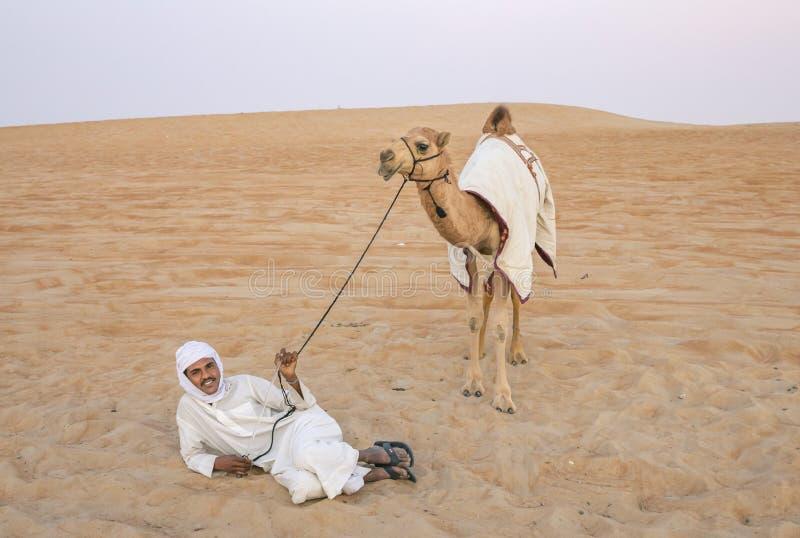 Homem com seu camelo em um deserto fotos de stock royalty free