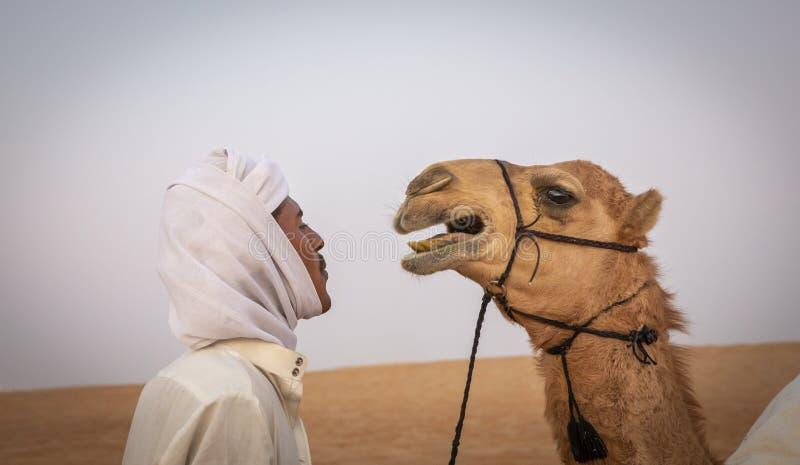 Homem com seu camelo em um deserto foto de stock