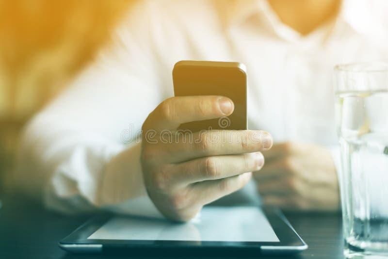 Homem com smartphone e tablet pc no restaurante fotografia de stock royalty free