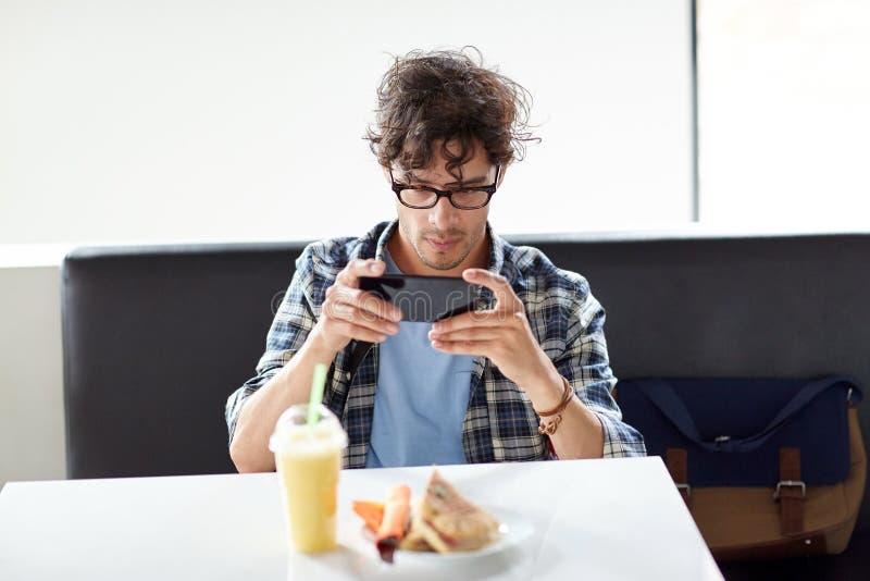 Homem com smartphone que fotografa o alimento no café imagem de stock