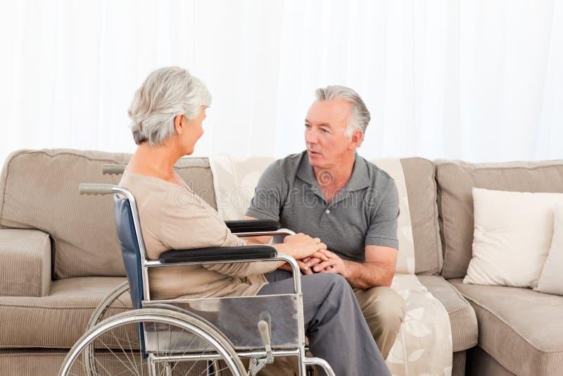 Homem com sua esposa em uma cadeira de rodas imagem de stock royalty free