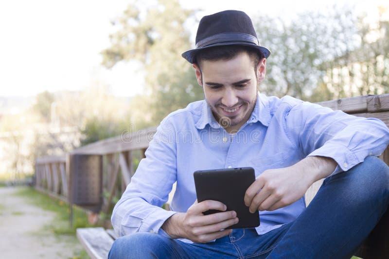 Homem com a tabuleta na rua imagem de stock