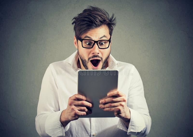 Homem com a tabuleta que olha chocada foto de stock royalty free
