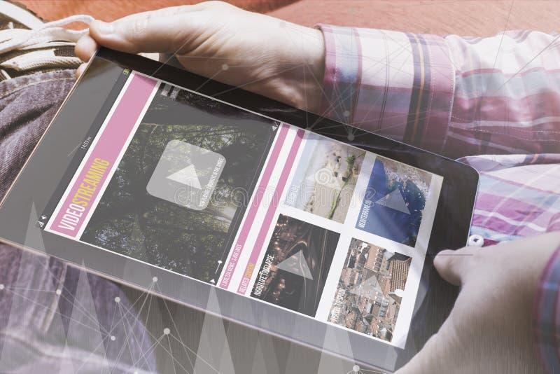 Homem com a tabuleta video do mercado no sofá fotografia de stock
