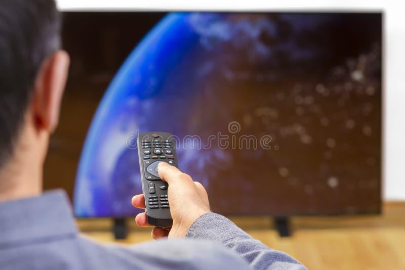 Homem com a tevê de observação de controle remoto fotos de stock