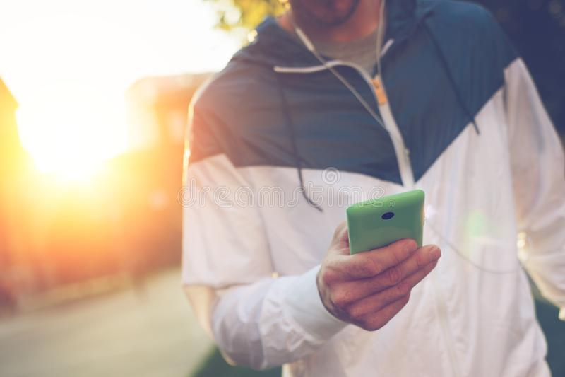 Homem com texto de datilografia do telefone celular e passeio na rua foto de stock