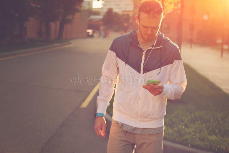 Homem com texto de datilografia do telefone celular, por do sol na rua imagem de stock royalty free