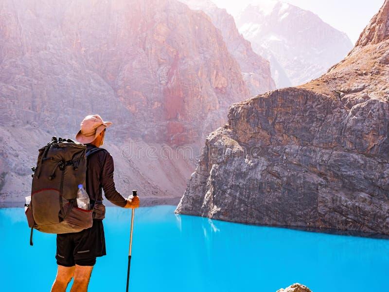 Homem com a trouxa perto do lago Alo grande no fundo da montanha rochosa imagem de stock royalty free