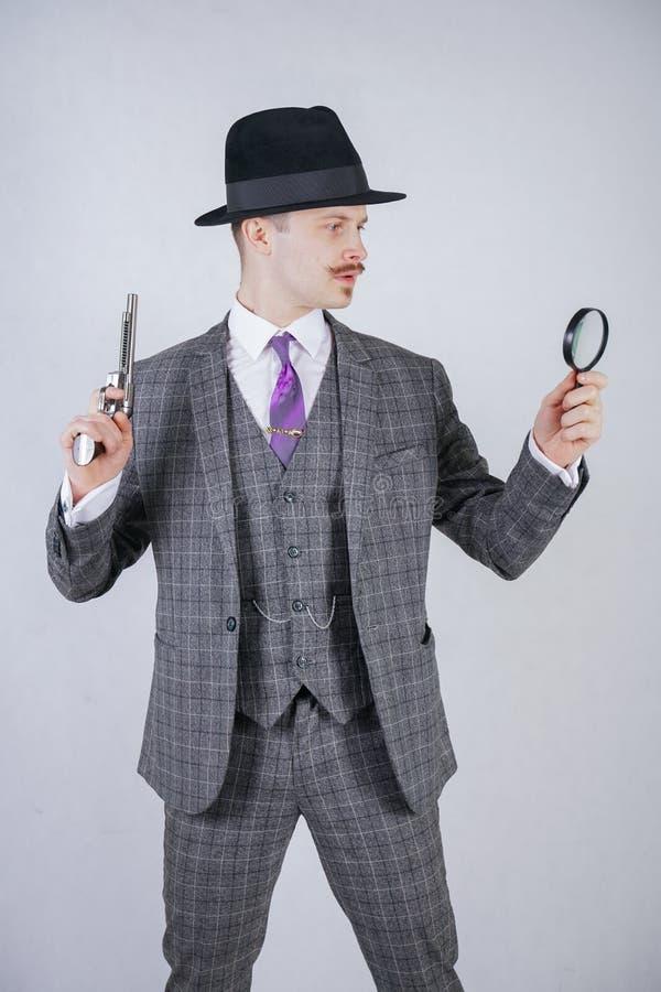 Homem com um bigode vestido em um terno da manta do negócio com um laço, retendo uma lupa e uma arma em um estúdio contínuo branc foto de stock