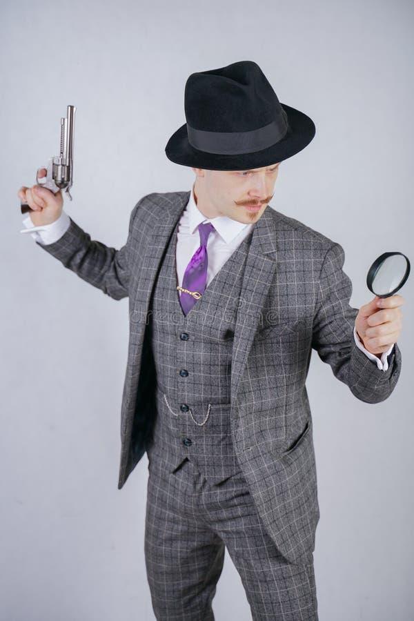 Homem com um bigode vestido em um terno da manta do negócio com um laço, retendo uma lupa e uma arma em um estúdio contínuo branc fotografia de stock royalty free