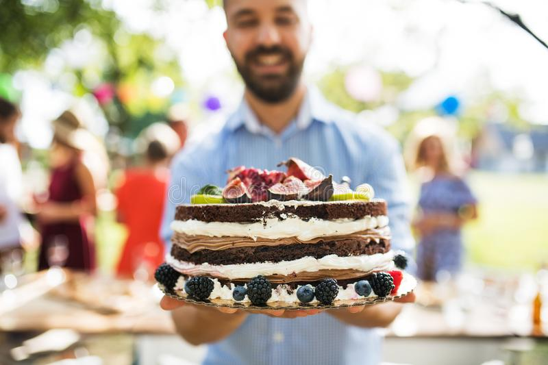 Homem com um bolo em uma celebração de família ou em um partido de jardim fora fotografia de stock royalty free