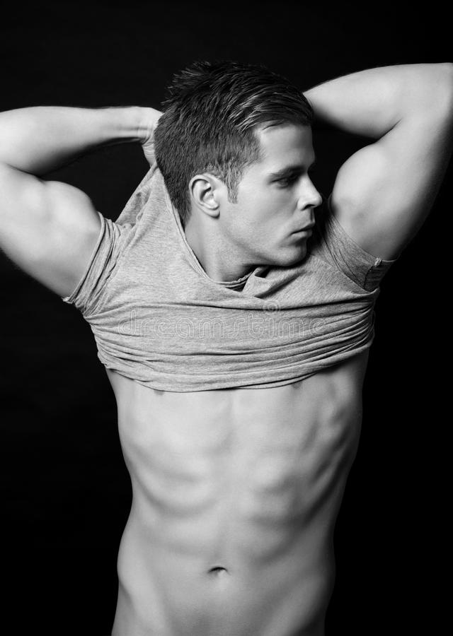 Homem com um corpo muscular no fundo preto foto de stock royalty free