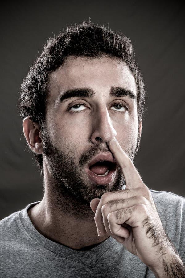 Homem com um dedo em seu nariz fotos de stock royalty free