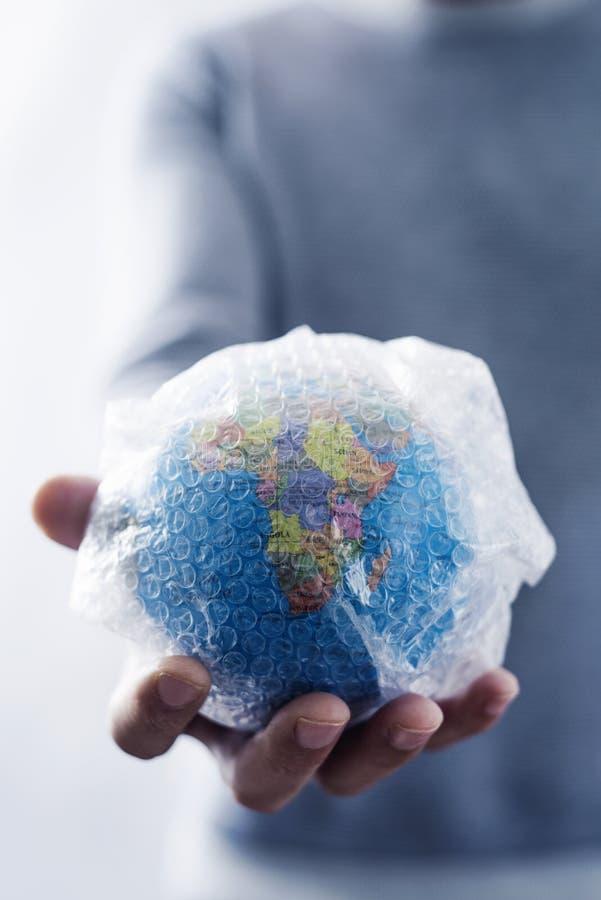 Homem com um globo do mundo envolvido no invólucro com bolhas de ar fotografia de stock