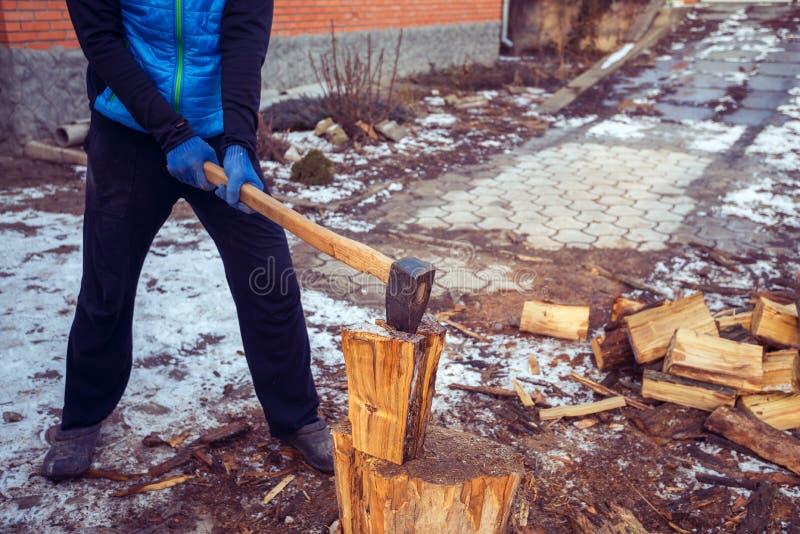 Homem com um machado em sua mão em processo da madeira do corte imagem de stock royalty free