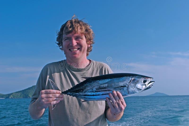Homem com um peixe foto de stock royalty free