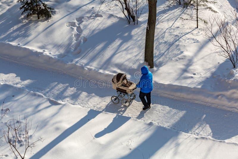 Homem com um transporte de bebê foto de stock royalty free