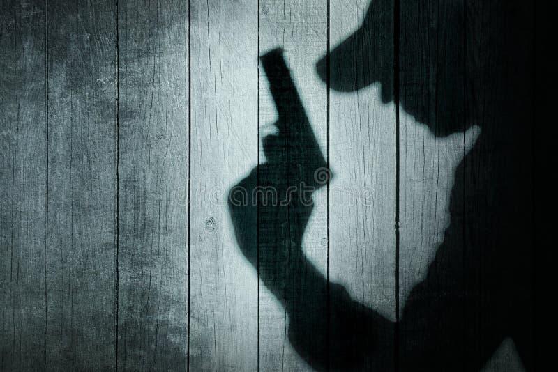 Homem com uma arma na sombra em um fundo de madeira fotografia de stock