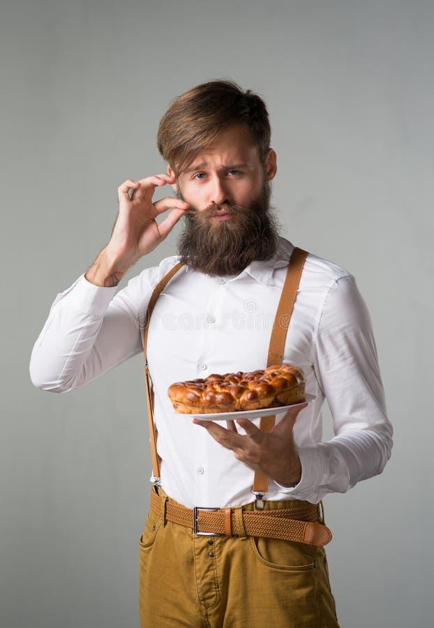 Homem com uma barba com uma torta imagens de stock royalty free