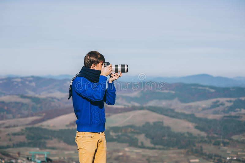 Homem com uma câmera na borda de um penhasco que negligencia as montanhas fotografia de stock royalty free