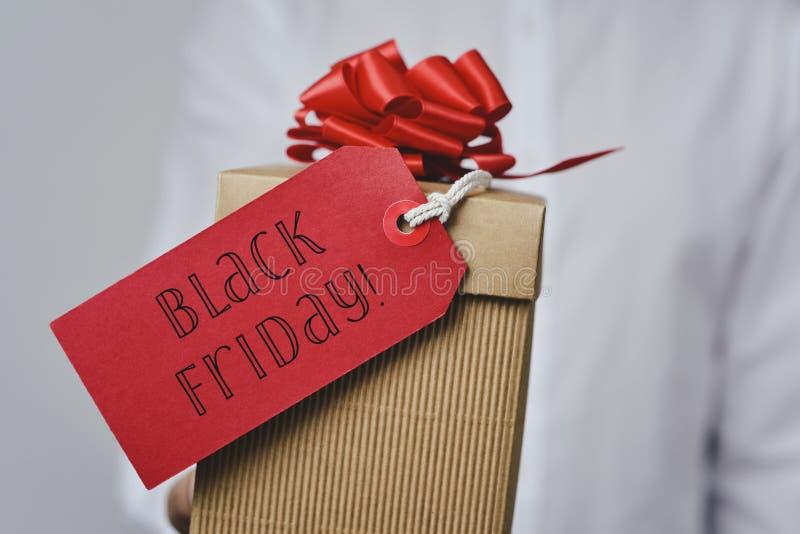 Homem com uma caixa de presente com o preto sexta-feira do texto fotografia de stock royalty free