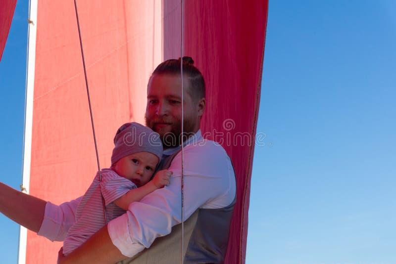 Homem com uma criança em um navio de navigação imagens de stock