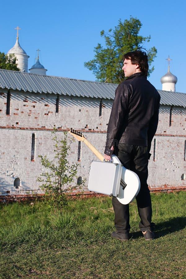 Homem com uma guitarra no campo imagem de stock royalty free