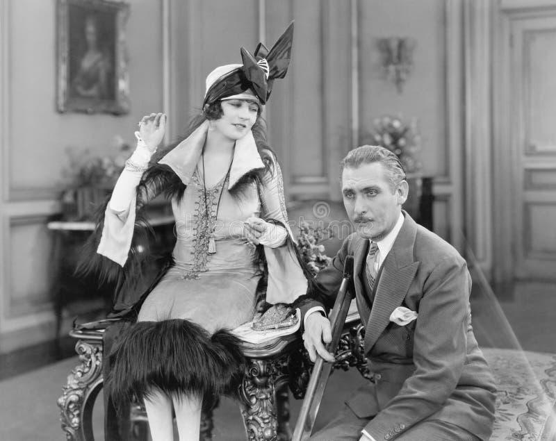 Homem com uma muleta e uma mulher que sentam-se junto em uma sala de visitas (todas as pessoas descritas não são umas vivas mais  fotografia de stock royalty free