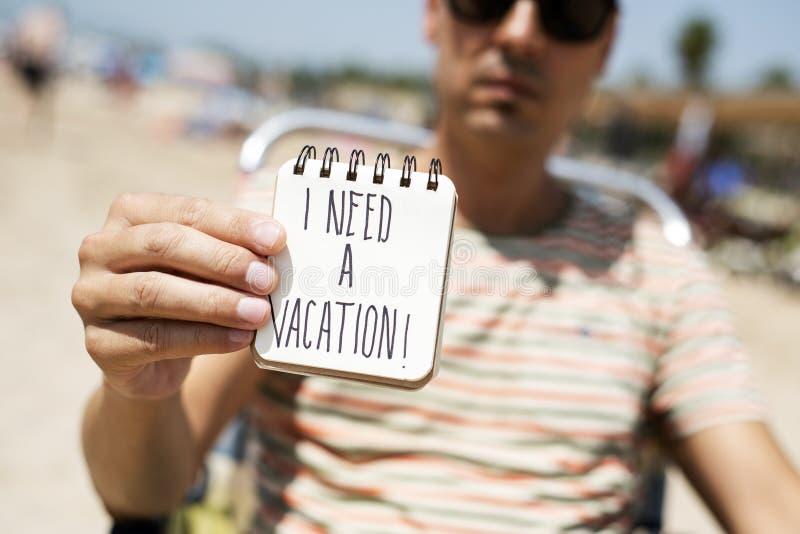 Homem com uma nota com o texto eu preciso umas férias fotografia de stock royalty free