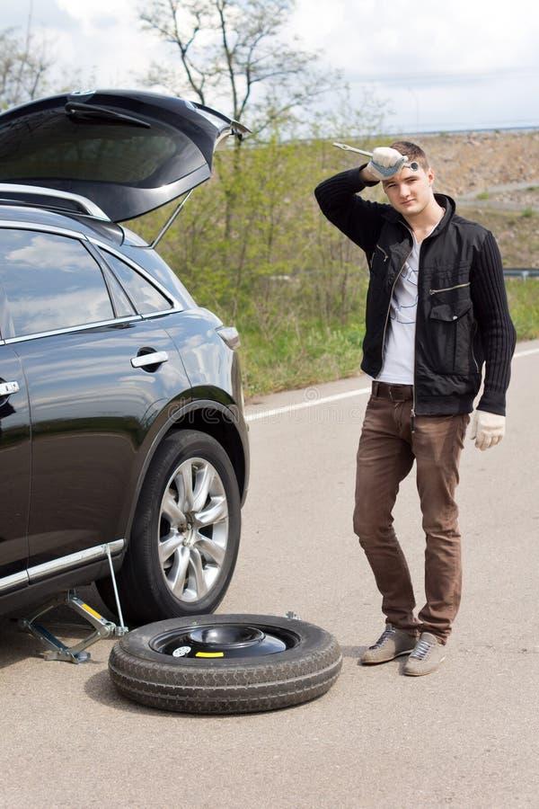 Homem com uma punctura que muda um pneumático fotografia de stock royalty free