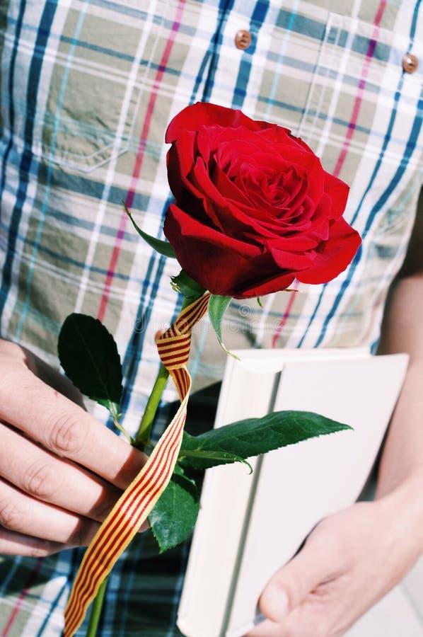 Homem com uma rosa com a bandeira Catalan e um livro imagens de stock