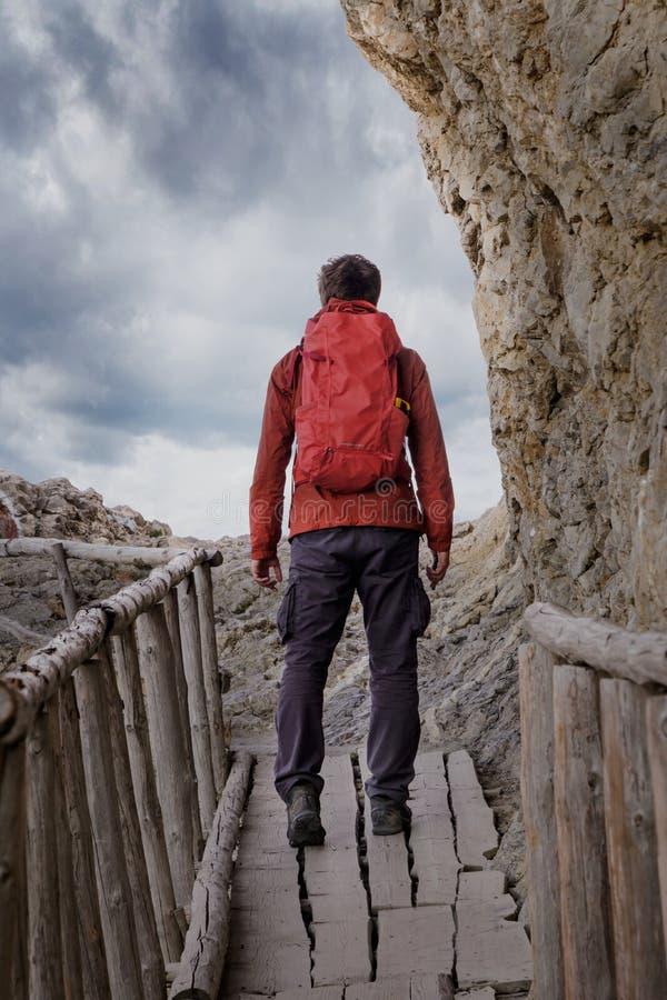Homem com uma trouxa durante uma caminhada em uma ponte de madeira velha fotografia de stock