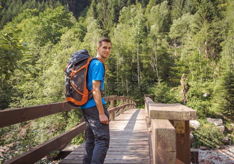 Homem com uma trouxa que anda em uma ponte na floresta imagens de stock royalty free