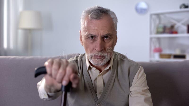 Homem com a vara de passeio que olha na câmera, anúncio sobre o auxílio para enfermos fotografia de stock