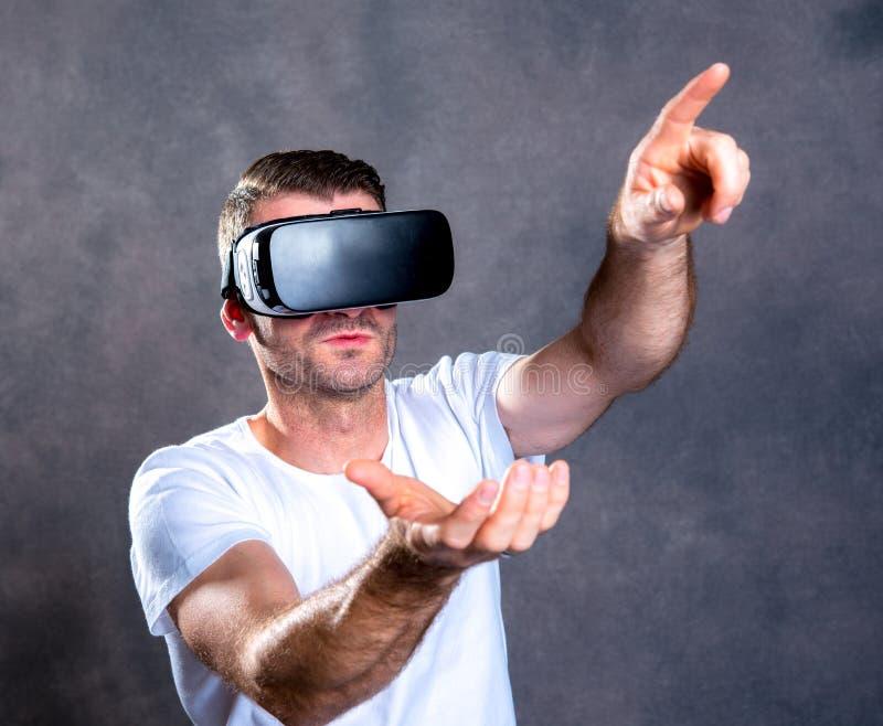 Homem com vidros da realidade virtual que aponta para cima fotografia de stock