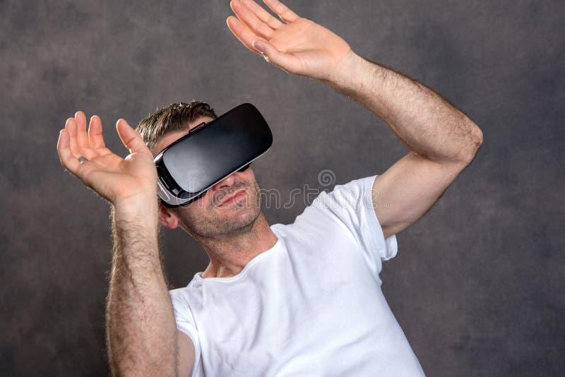 Homem com vidros da realidade virtual que aponta a vista surpreendido imagem de stock royalty free