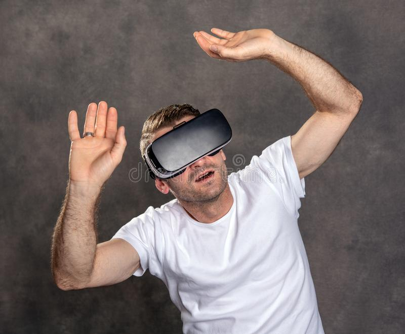 Homem com vidros da realidade virtual que aponta a vista surpreendido foto de stock