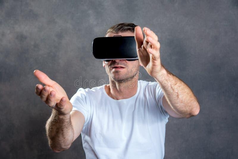 Homem com vidros da realidade virtual que aponta a vista surpreendido fotos de stock royalty free