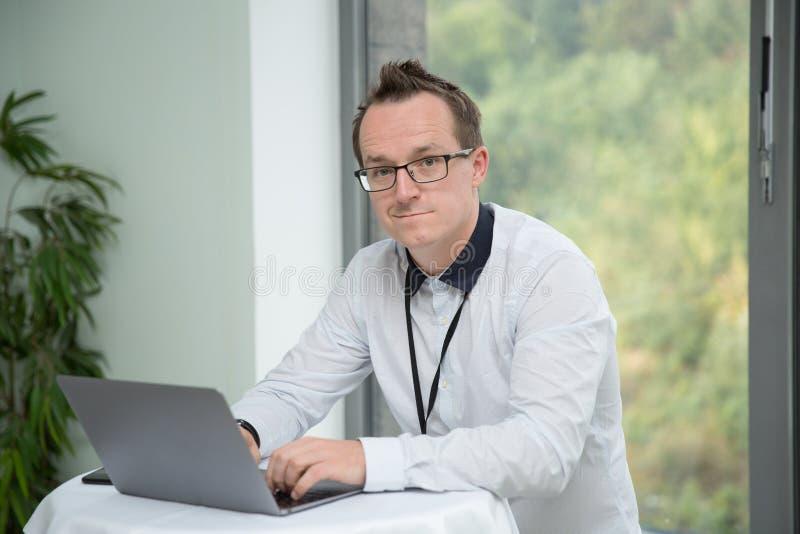 Homem com vidros que datilografa no portátil imagem de stock royalty free
