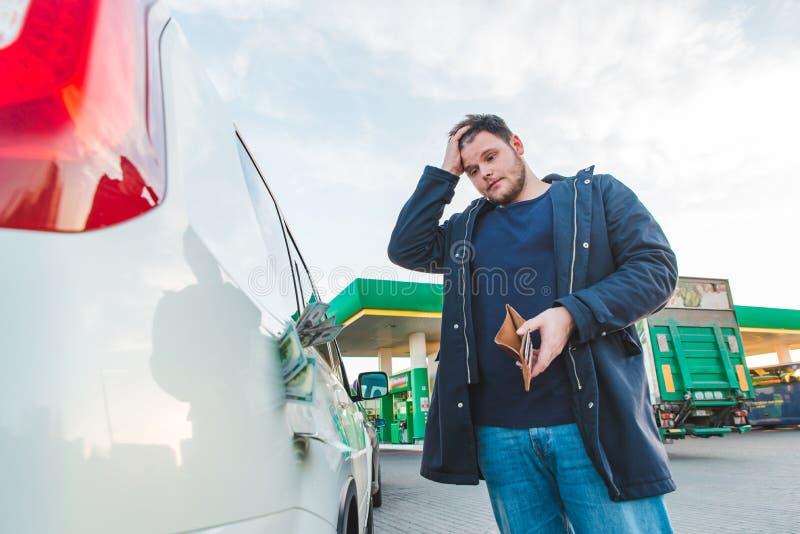Homem com vista triste e carteira vazia no posto de gasolina Dólares do dinheiro imagem de stock royalty free