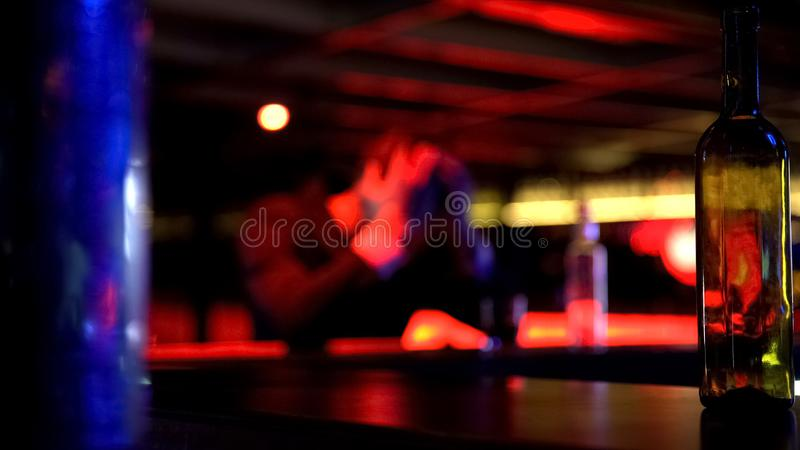 Homem comprimido que bebe apenas no clube noturno, pensando sobre problemas, defocused imagens de stock