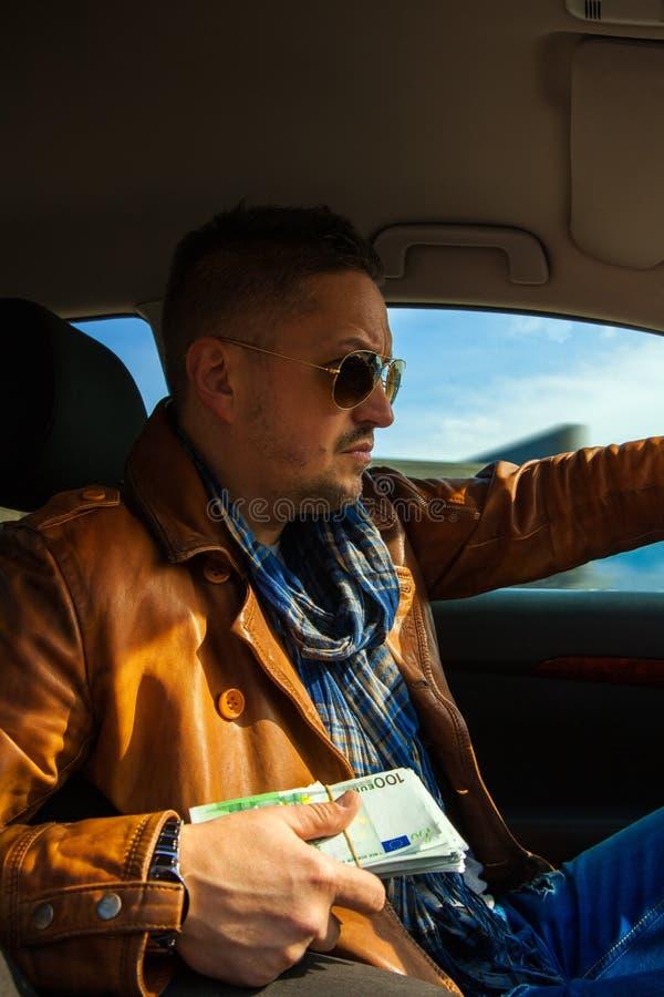 Homem concentrado nos óculos de sol com o pacote de dinheiro no dri das mãos imagem de stock