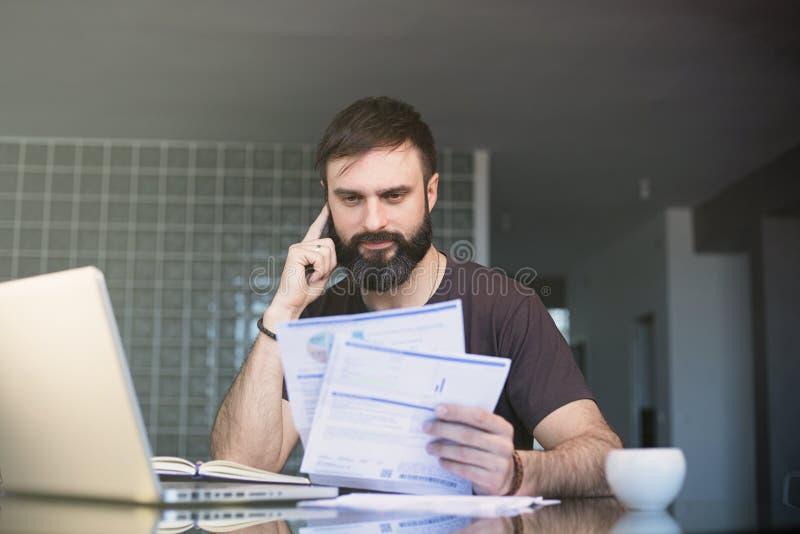 Homem concentrado positivo farpado que trabalha no portátil e que senta-se na tabela ao olhar os papéis e ao guardar seu imagens de stock royalty free