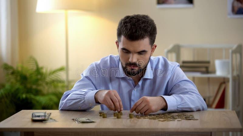 Homem concentrado que conta o dinheiro na tabela, inflação do preço, trabalho baixo-pago, economias imagens de stock