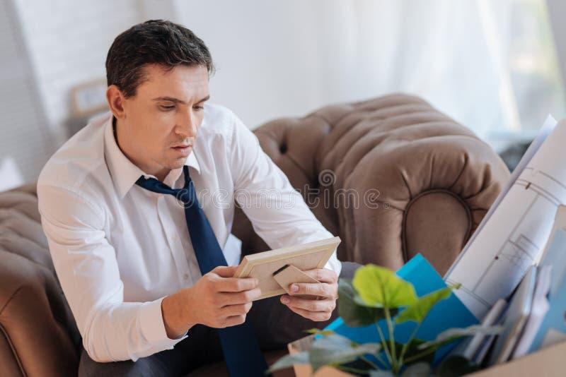Homem concentrado sério que senta e que olha a foto em um quadro fotografia de stock royalty free