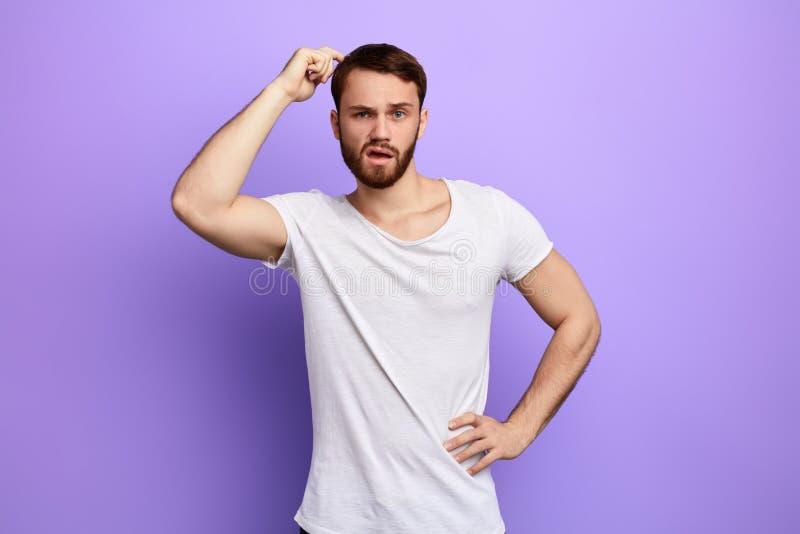 Homem confundido e confuso com uma mão na cabeça de risco anca fotografia de stock