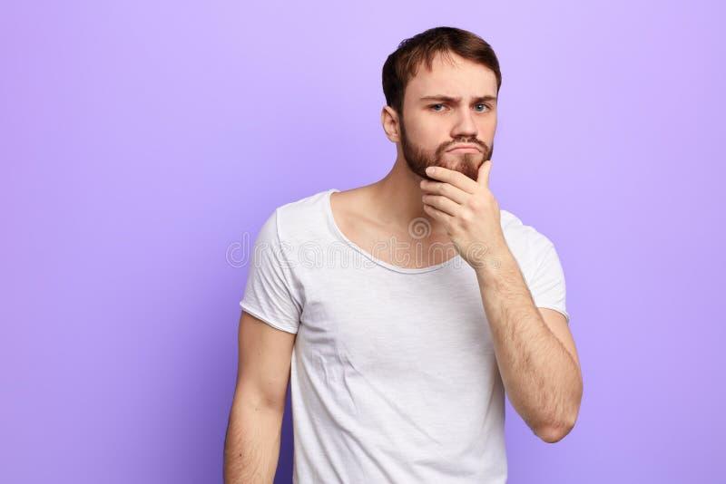 Homem confundido novo que pensa sobre o problema foto de stock royalty free