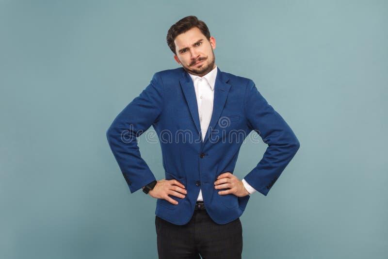 Homem confuso bem vestido que está e que olha a câmera imagem de stock