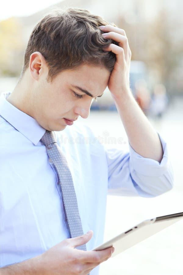 Homem confuso que olha a tabuleta digital fotografia de stock royalty free
