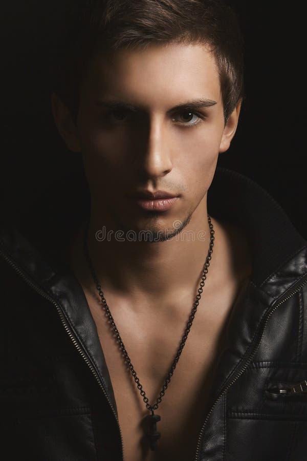 Homem considerável à moda, muscular com um corpo forte perfeito no casaco de cabedal preto no corpo despido que levanta no preto imagem de stock royalty free